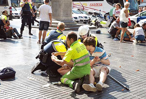 Spanish policemen and medics tend to the injured after a van plowed into a crowd on the Rambla, Barcelona's most popular street, on Aug.17, 2017. AFP-GETTY IMAGES