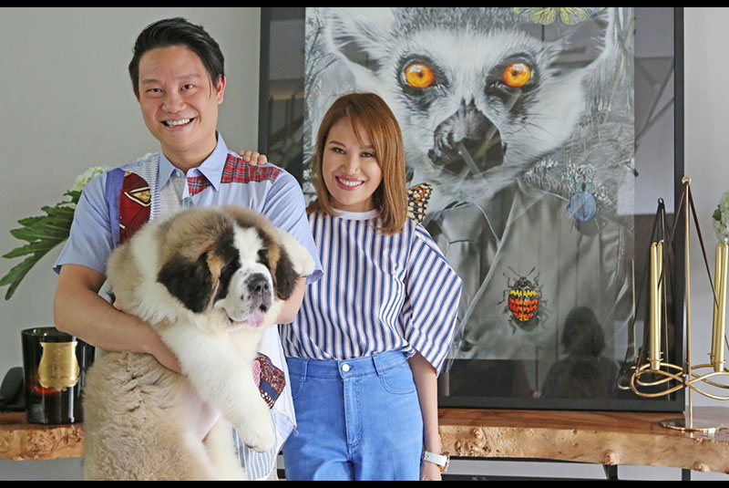 Loving animals and art: Doctors Z Teo and Aivee Teo with Barney the St. Bernard beside an untitled painting by Andres Barrioquinto. Photos by WALTER BOLLOZOS