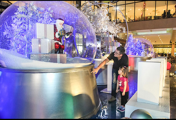 """Hey, Father Christmas!: This young girl is mesmerized by the giant snow globe featured in Pandora's """"Magic of Christmas"""" installation at Greenbelt 5."""