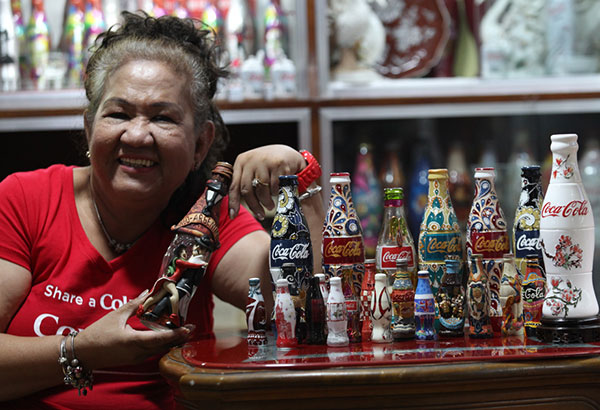 "Consuelo ""Ching"" Santiago with her favorite Coca-Cola bottle from Argentina and the other special edition Coca-Cola bottles from other countries. Photos bye JUN MENDOZA"