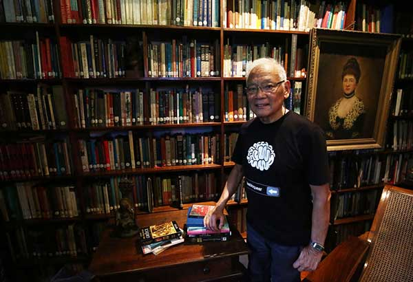 """Dr. Jaime Laya at home with his collection of books: """"I normally have five bedside books at a time."""" Photo BY MIGUEL DE GUZMAN"""