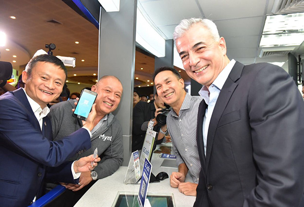 Jack Ma tries the Scan to Pay feature of GCash at the Glorietta cinema ticket booth with Globe president and CEO Ernest Cu, Ayala Land president and CEO Bobby Dy, and Ayala Corporation president and COO Fernando Zobel de Ayala.