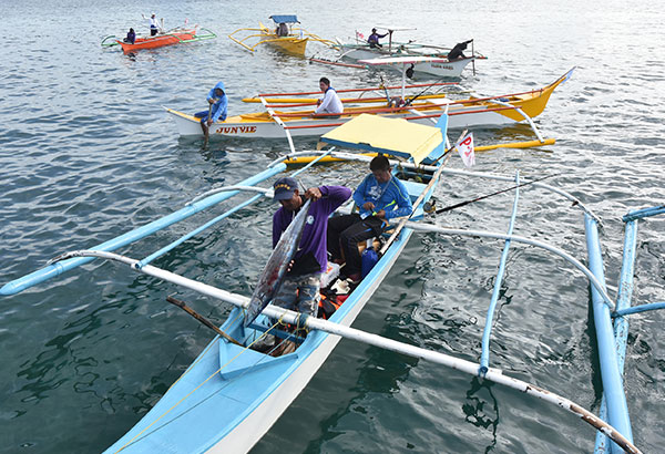 A boatman and his angler unload their catch at the 10th Siargao International Game Fishing tournament in Pilar, Siargao.