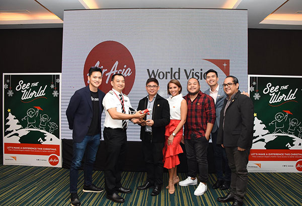 AirAsia executives hand over an AirAsia model plane as a sign of commitment and partnership with World Vision. (From left) AirAsia regional COO Pete Chareonwongsak, AirAsia Philippines' chief pilot for operations Capt. Darren Adrian Acorda, World Vision Phils. national director Rommel Villafuerte, World Vision ambassadors Gelli Victor, Quest and Christian Bautista and World Vision Phils. media communications manager Gjeff Lamigo.