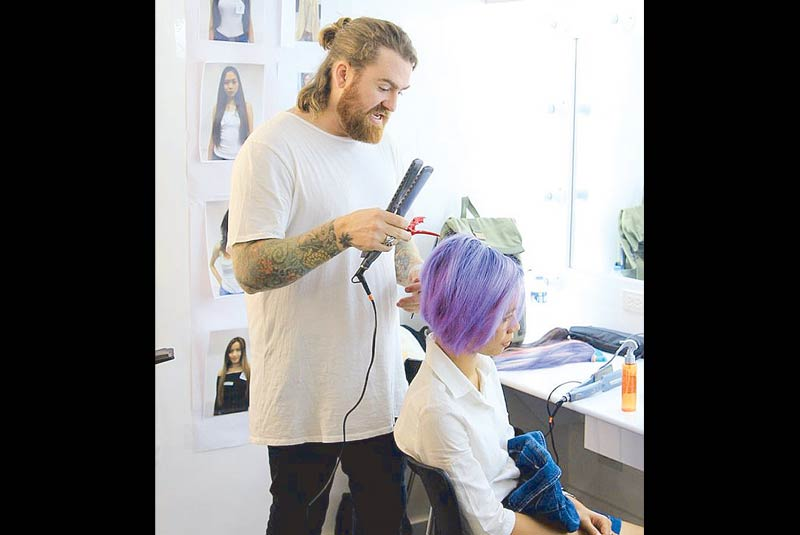 Purple power: Hairstylist Matthew Collins styles a model with bright-colored locks.