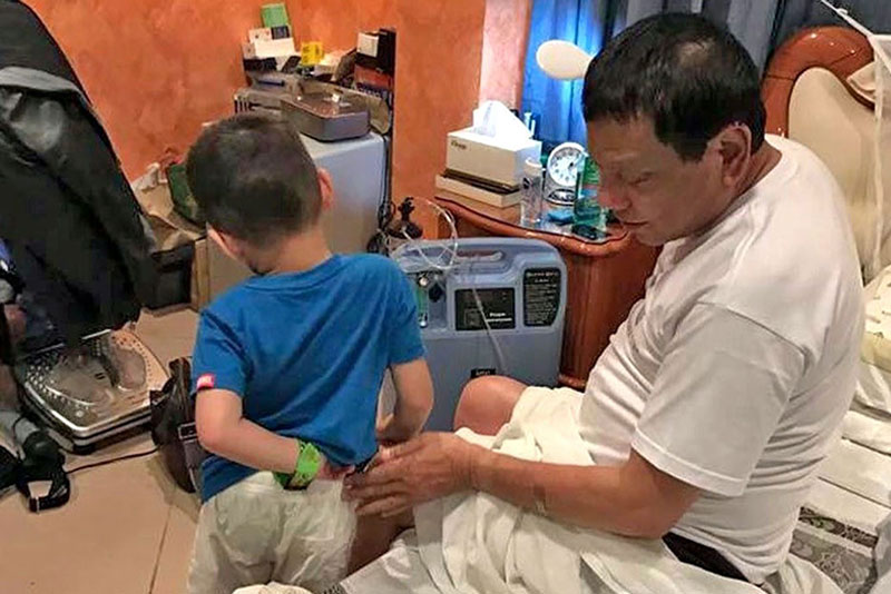 Photo taken during President Duterte's birthday shows him in his bedroom with one of his grandchildren and beside an oxygen-converter.