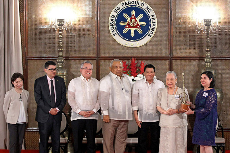 Socorro Ramos, founder of National Bookstore, receives one of the Inspiring Filipina Entrepreneurs Awards from President Duterte at Malacañang yesterday. Also in photo are (from left) Tessie Sy-Coson, vice chair of SM Investments Corp., presidential adviser for entrepreneurship and Go Negosyo founder Joey Concepcion, Trade Secretary Ramon Lopez, Executive Secretary Salvador Medialdea and Xandra Ramos-Padilla, NBS managing director.                 KRIZJOHN ROSALES