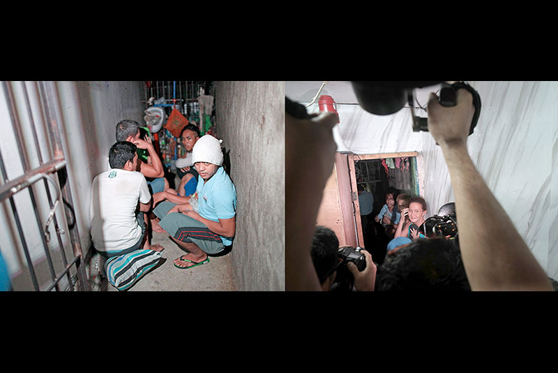 Detainees huddle in a makeshift detention cell hidden behind a shelf in the Manila Police District's Drug Enforcement Unit office yesterday. MIGUEL DE GUZMAN