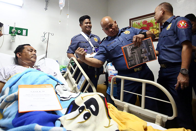 PNP chief Director General Ronald dela Rosa shares a light moment with Police Officer 3 Michael Carabeo and Police Officer 1 Ronald Dipacina at the UST Hospital yesterday. MIGUEL DE GUZMAN
