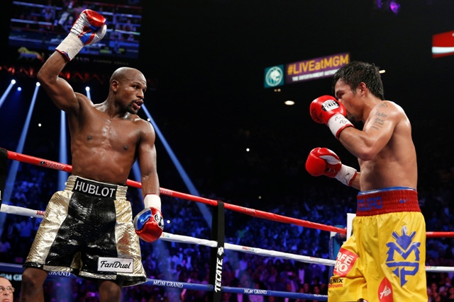 Floyd Mayweather Jr., left, celebrates during his welterweight title fight against Manny Pacquiao, from the Philippines, on Saturday, May 2, 2015 in Las Vegas. AP/John Locher