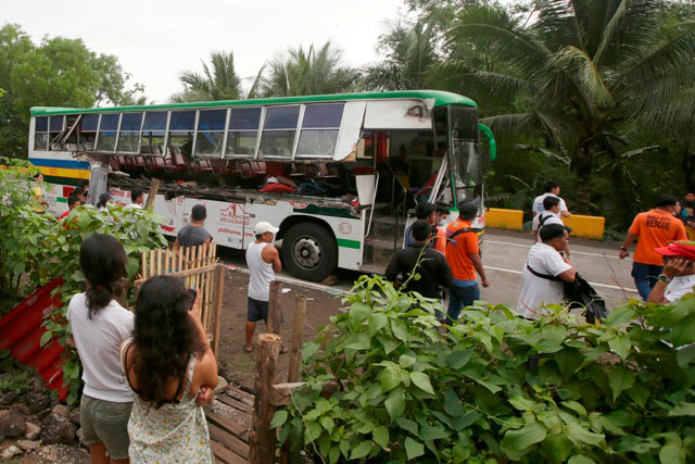 Residents and rescuers look at a passenger bus after it rammed into a cargo truck early Wednesday, April 16, 2014 along a highway at Libmanan township, Camarines Sur province. AP/Bullit Marquez