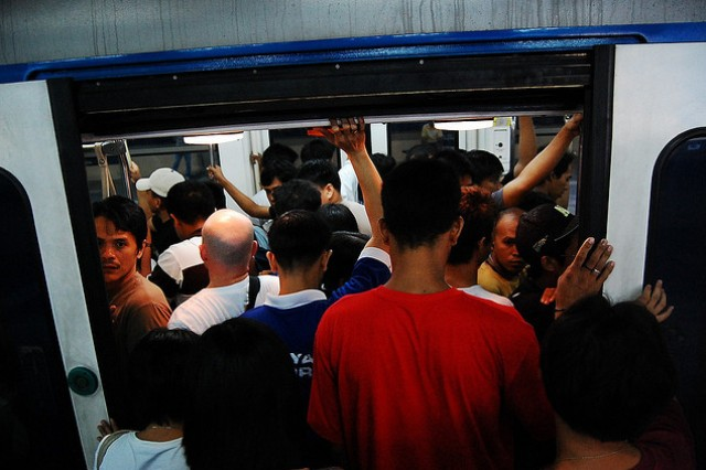 Male passengers push their way into a crowded Metro Rail Transit 3 train along EDSA, a major thoroughfare in Metro Manila. Jong Pairez/ CC BY-NC-SA
