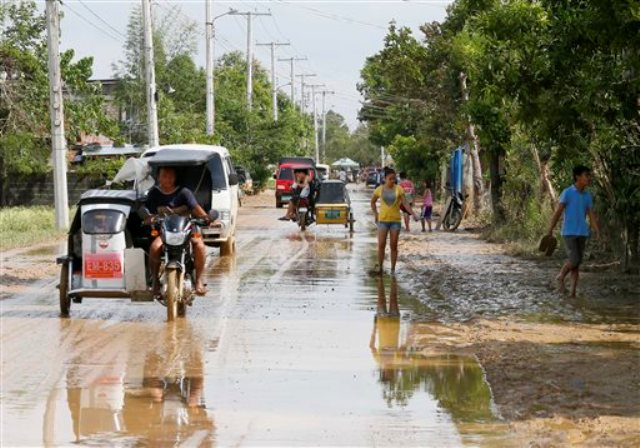 Residents move through streets full of mud and flood waters in Cabanatuan city on Tuesday, Oct. 20, 2015, two days afterTyphoon Lando battered the northern part of the country earlier this week.AP/Bullit Marquez