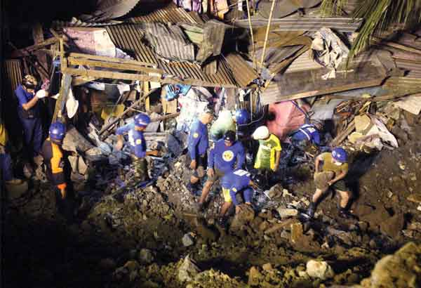 Rescue personnel work to find the body of a girl who was buried when the riprap of a government road project collapsed in Cogeo, Antipolo on Saturday. Bernardo Batuigas