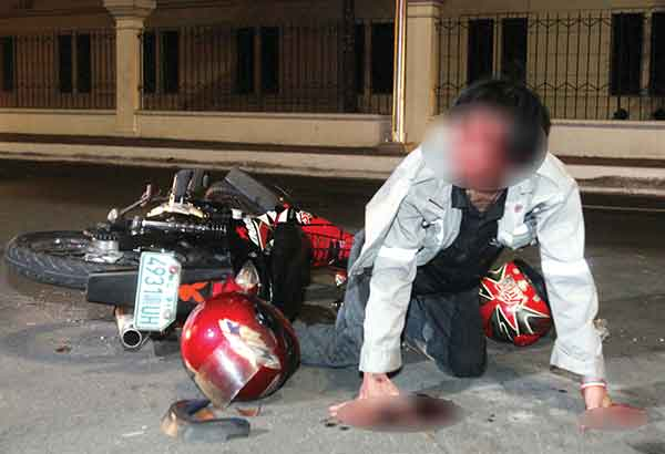 Ramil dela Cruz tries to get up after crashing his motorcycle along Finance Road in Manila before dawn on Nov. 18. He was reportedly driving while drunk. BERNARDO BATUIGAS