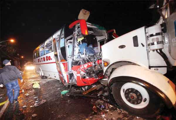 A traffic investigator examines a bus and a trailer truck that collided in Silang, Cavite on Saturday night. Bernardo Batuigas