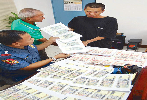 Batasan police station chief Superintendent Robert Sales shows the fake money seized from Datu Ali and Mohamad Makakina in Quezon City on Thursday. BOY SANTOS