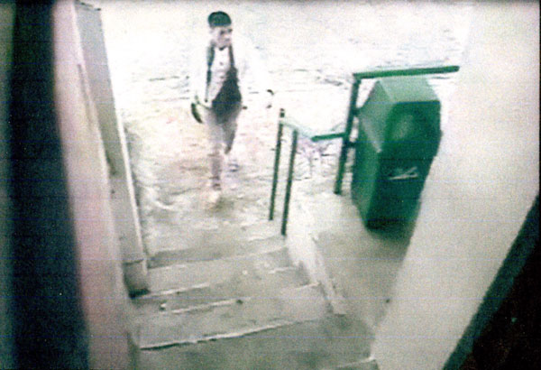 A still from a closed-circuit television video shows a man, later identified as the killer of housewife Susan Tan-Uy, approaching the entrance to a store near the victim's house minutes before she was attacked on Dec. 24, 2015.