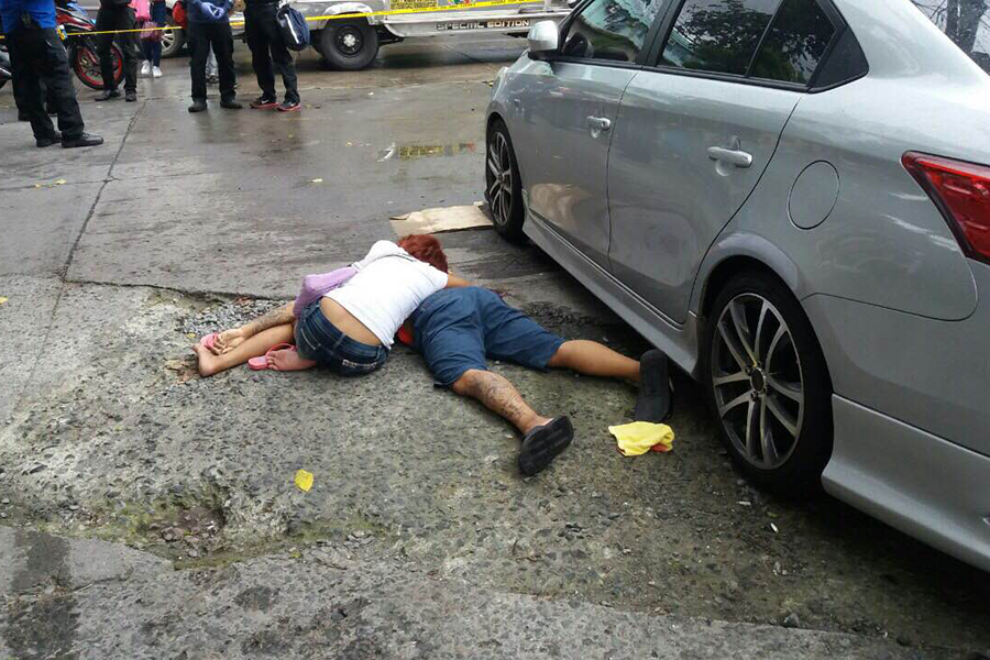 The victim's live-in partner weeps at the lifeless body of her partner on the street. Makati police