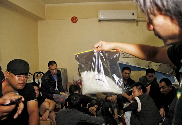 A PDEA agent examines a pack of shabu in front of some of the 25 Chinese arrested during a raid on a unit at the Bayview Tower condominium in Parañaque City yesterday.