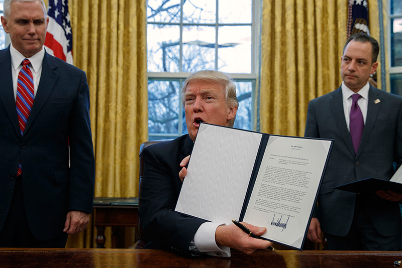 In this Monday, Jan. 23, 2017 file photo, Vice President Mike Pence, left, and White House Chief of Staff Reince Priebus, right, watch as President Donald Trump shows off an executive order to withdraw the U.S. from the 12-nation Trans-Pacific Partnership trade pact agreed to under the Obama administration in the Oval Office of the White House in Washington. AP/Evan Vucci, File
