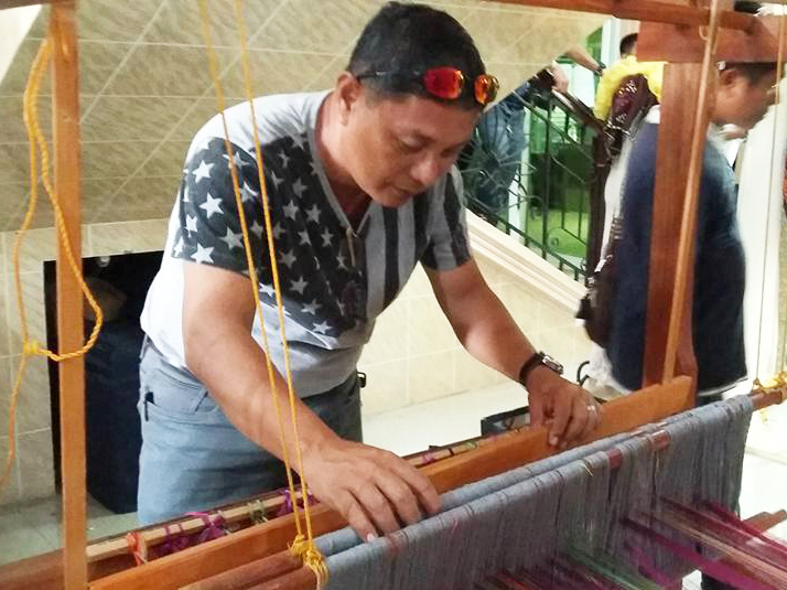 "Entrepreneur-tourist Melvyn Avanceña Aradanas tries a wooden loom for weaving Inaul cloth, one of many now on display in Buluan, Maguindanao to highlight the first ever ""Inaul Festival"" in the province. Philstar.com/John Unson"