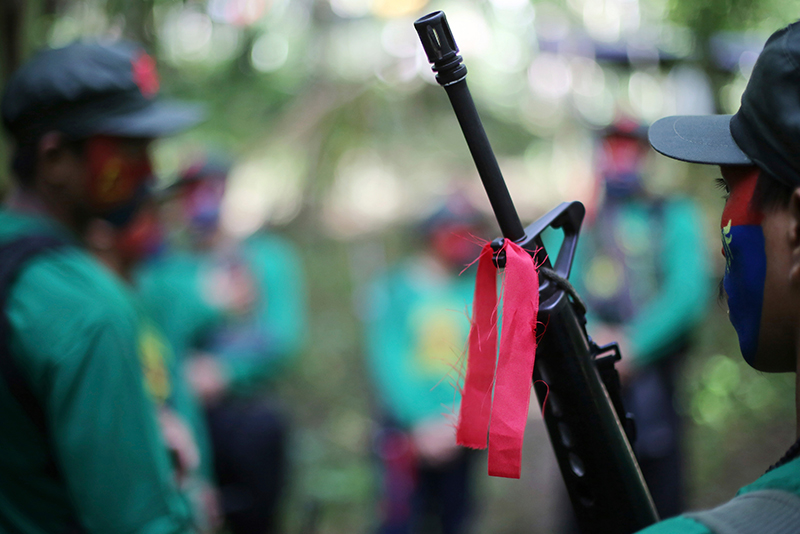 In this Nov. 23, 2016 photo, a red ribbon is tied to a firearm of a New People's Army guerrilla at a rebel encampment tucked in the harsh wilderness of the Sierra Madre mountains. AP/Aaron Favila
