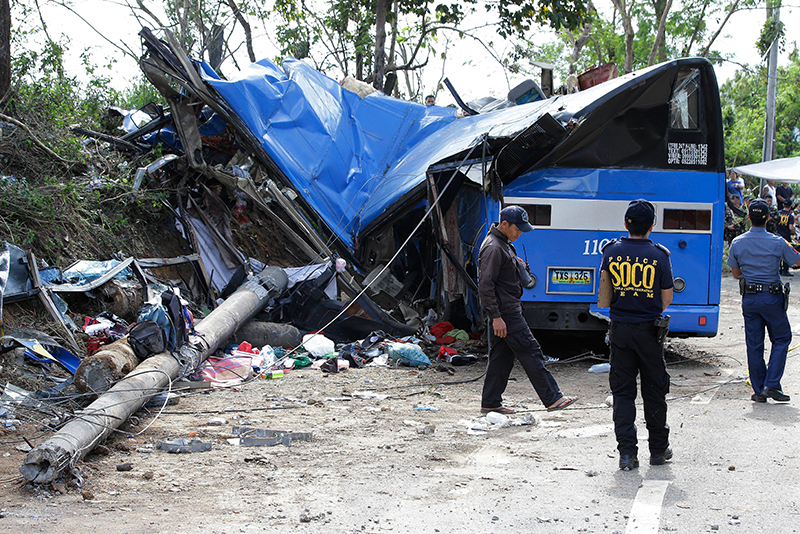 Police investigators stand beside the wreckage of a bus that crashed on a downhill road in Tanay, Rizal province, Philippines, Monday, Feb. 20, 2017. More than a dozen mostly college students on a camping trip were killed when their rented bus lost its brakes on the downhill road slammed into a post, town officials said. AP/Aaron Favila