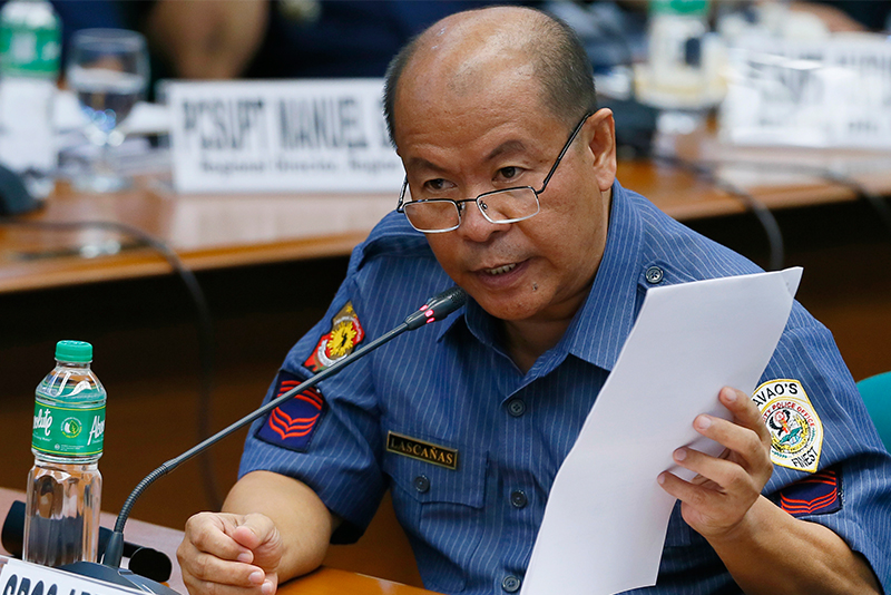 Retiring police officer Arthur Lascañas, who was frequently mentioned by another witness Edgar Matobato allegedly as having an extensive knowledge of the extrajudicial killings in President Rodrigo Duterte's hometown of Davao city, holds some documents during a Senate inquiry in October 2016. Lascañas resurfaced on Monday, Feb. 20, 2017 and admitted involvement in the Davao Death Squad. AP/File