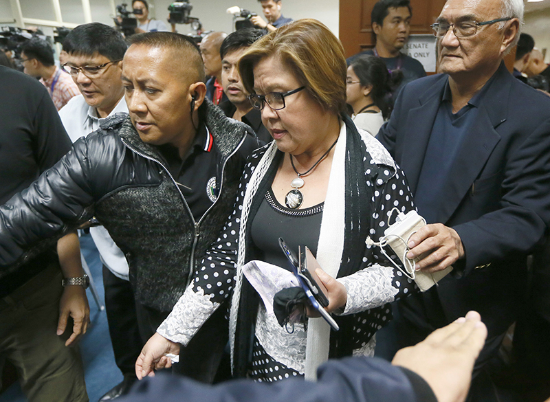 Sen. Leila de Lima is escorted by Senate security to address the media after a warrant for her arrest was issued by a regional trial court Thursday, Feb. 23, 2017. AP/Bullit Marquez