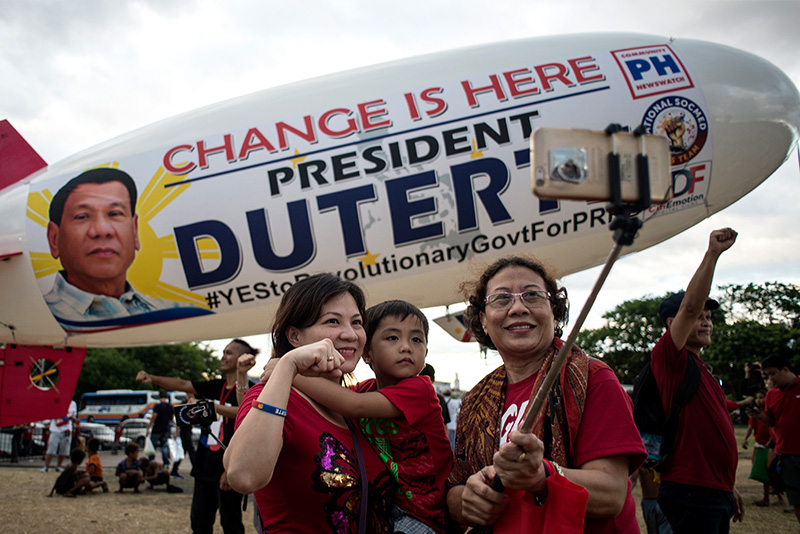 Supporters of Philippine President Rodrigo Duterte pose in front of a blimp for a picture during a protest calling for the ouster of Vice President Leni Robredo over his drug war criticism, in Manila on April 2, 2017. Thousands of supporters of Philippine President Rodrigo Duterte held a protest in Manila on April 2, calling for the removal of Vice President Leni Robredo from office for criticising Duterte's deadly war on drugs before the United Nations. AFP/Noel Celis