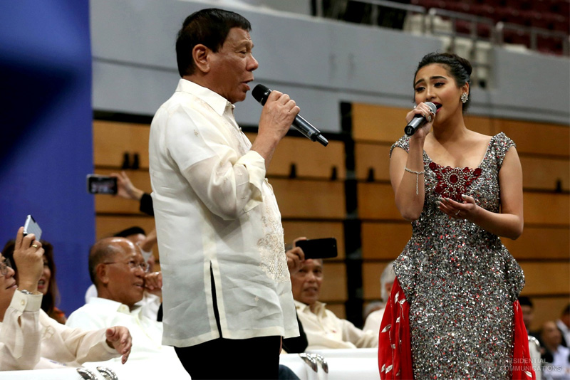 """President Rodrigo Duterte sings with a performer who sang one of his favorite songs """"Ikaw"""" in an intermission number during the meeting with Filipinos at the Lusail Sports Arena in Lusail, Qatar on April 15, 2017. PPD/Simeon Celi"""
