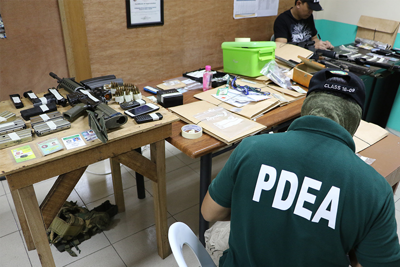 PDEA-ARMM agents examine firearms and drugs seized in a raid in Sultan Kudarat town in Maguindanao in May. Philstar.com/John Unson, file