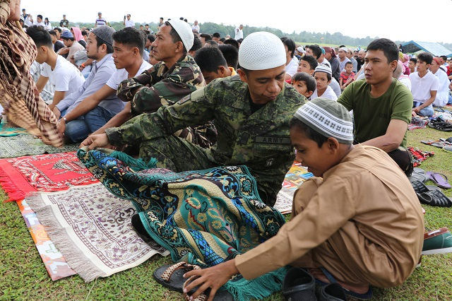 A soldier helps a child lay a prayer carpet just before Sunday morning's outdoor Eid'l Fitr rite at Camp Siongco in Maguindanao. JOHN UNSON