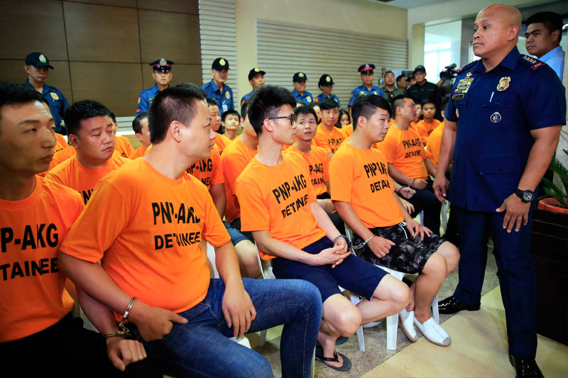 PNP chief Director General Ronald dela Rosa talks to some of the 43 for- eigners, arrested for kidnapping, during a press conference at Camp Crame yesterday. Photos below show alleged gang leader Chen DeQin and Ah-Wing Zhang, who remain at large. Boy Santos, Cecille Suerte Felipe
