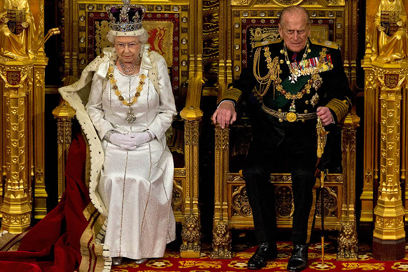 In this Wednesday, May 9, 2012 file photo Britain's Queen Elizabeth II sits next to Prince Philip in the House of Lords as she waits to read the Queen's Speech to lawmakers in London. Britain's Prince Philip on Wednesday Aug. 2, 2017 retires from solo official duties. Over the decades he has become renowned for his stalwart support of his wife, Queen Elizabeth II. AP/Alastair Grant, File