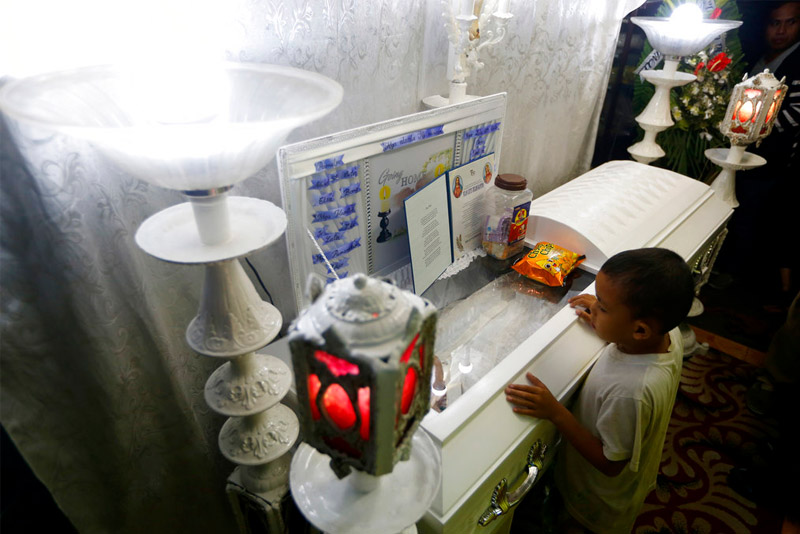 Jomari (only one name given), a neighbor and friend of slain Kian Loyd Delos Santos, refuses to leave the wake of his friend Friday, Aug. 18, 2017 in Caloocan City, Philippines. Kian Loyd, a 17-year-old Grade 11 student, was killed on Wednesday allegedly in a shootout with police. The killing of Kian has sparked protests and condemnation from concerned citizens. AP/Bullit Marquez