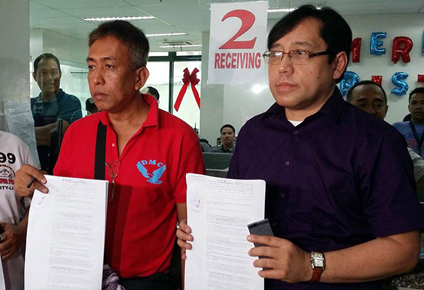 Taxi driver Virgilio Doctor (left) and Ariel Inton of the Lawyers for Commuters Safety and Protection show copies of the charges Doctor filed with the Quezon City prosecutor's office yesterday. Emmanuel Tupas
