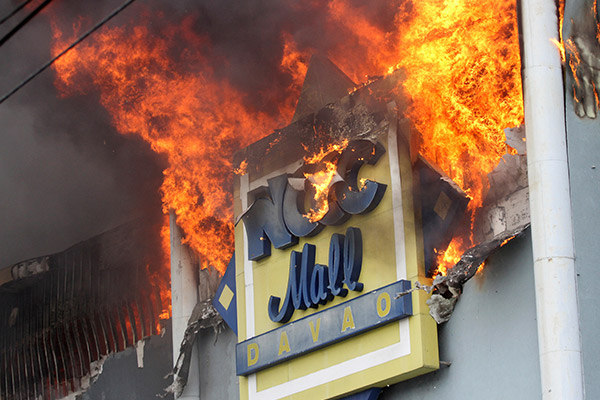 A fire rages on at a shopping mall Saturday, Dec. 23, 2017, Davao city, southern Philippines. As the fire continues to burn, an undetermined number of people are trapped inside, fire officials said.AP Photo/Manman Dejeto