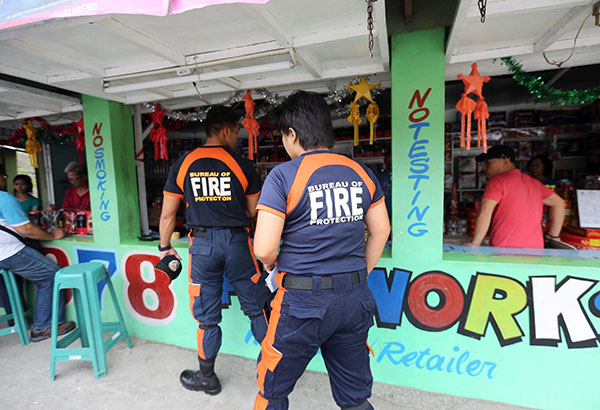 Bureau of Fire Protection personnel inspect a fireworks store in Barangay Turo, Bocaue, Bulacan yesterday. Boy Santos