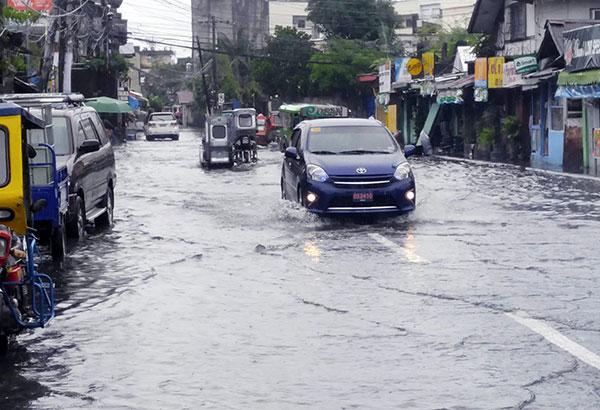 Motorists cross a flooded street in Barangay Orosite, Legazpi, Albay yesterday. Celso Amo