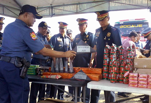 Sta. Maria, Bulacan police chief Superintendent Rainel Valones (left) presents illegal firecrackers seized during the inspection of fireworks stores in Barangay Turo, Bocaue, Bulacan yesterday. Ramon Efren Lazaro