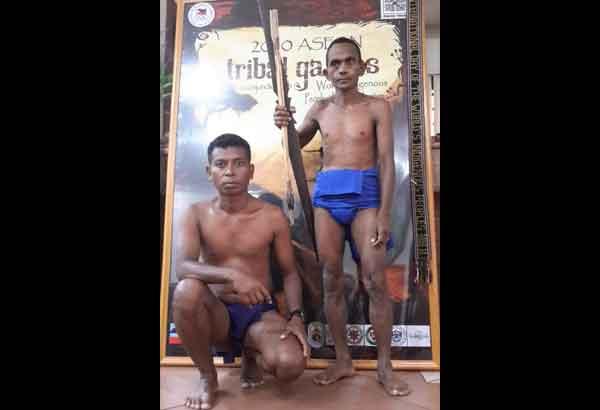 Aeta athletes Jung Ablong (left) and Dumlao Naval pose in front of a poster of the first ASEAN tribal olympics held in Malaysia in 2010, wherein they emerged champions in archery. DING CERVANTES