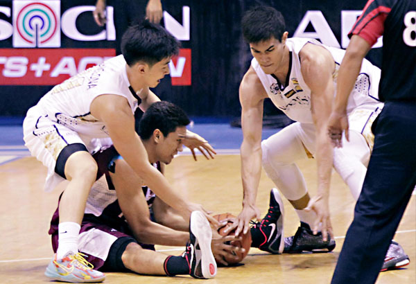 UP Maroon Dave Moralde hangs on to the ball as Nico Javelona (left) and Jeth Rosario of National U stoop down to grab it in a UAAP thriller yesterday at the Mall of Asia Arena. JUN MENDOZA