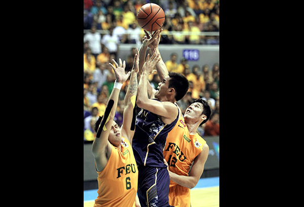 National U's Jeth Troy Rosario (center) squeezes out a tight shot against FEU's Raymar Jose (left) and Mac Belo during Game Two of the UAAP men's basketball finals at the Big Dome.              JOEY MENDOZA JR.