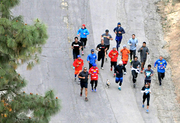 Filipino champ Manny Pacquiao pounds the mountain roads around Griffith Park in Los Angeles in an early morning workout with friends and pet Jack Russell terrier Pacman. ABAC CORDERO