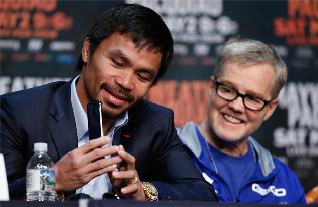 Manny Pacquiao, left, shows his phone to trainer Freddie Roach during a news conference Wednesday, April 29, 2015, in Las Vegas. Pacquiao will face Floyd Mayweather Jr. in a welterweight boxing match in Las Vegas on May 2. AP Photo/John Locher