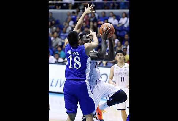 NU Bulldog Alfred Aroga goes to the basket against Blue Eagle Gideon Babilonia in their game yesterday at the Araneta Coliseum.