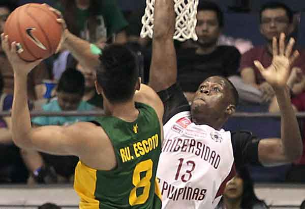 FEU Tamaraw Russel Escoto takes a shot against Cheick Kone of UP in their UAAP game yesterday at the Big Dome.  JUN MENDOZA