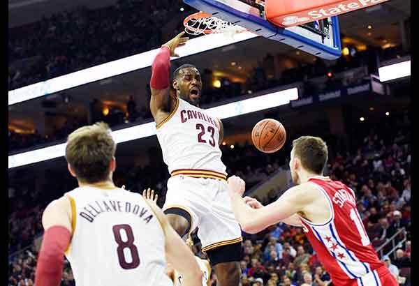 Cleveland's LeBron James dunks over Philadelphia's Nik Stauskas